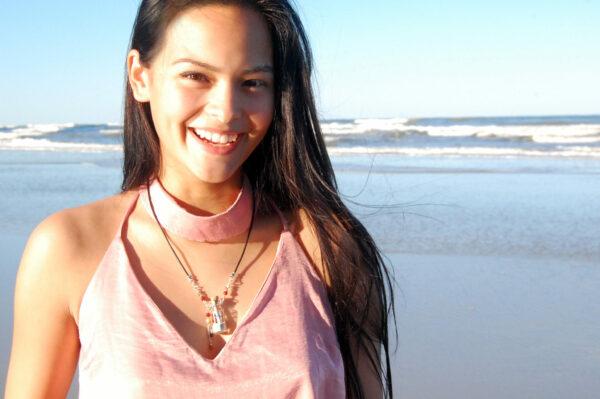 Smiling girl wearing Gidget's Getaways Beach in a Bottle